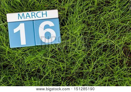 March 16th. Day 16 of month, calendar on football green grass background. Spring time, empty space for text.