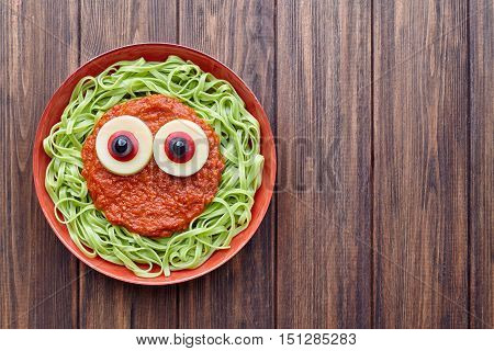 Green spaghetti creative pasta scary halloween food vampire monster with fake blood tomato sauce and funny big mozzarella eyeballs decoration kid party meal on vintage table.