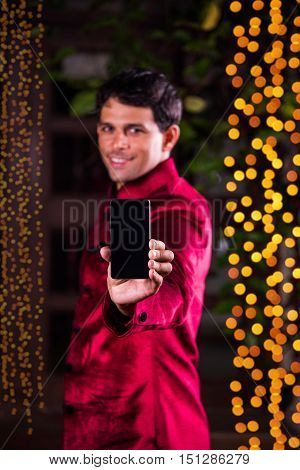 Young indian man showing smart phone screen against diwali lighting  background. indian man celebrating diwali with smartphone showing blank screen