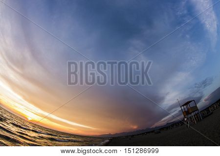 the four elements in a fish-eye image, the sea, the bright orange sun, the stormy sky and sand