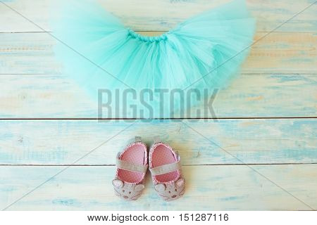 Tutu skirt with booties on turquoise wooden background