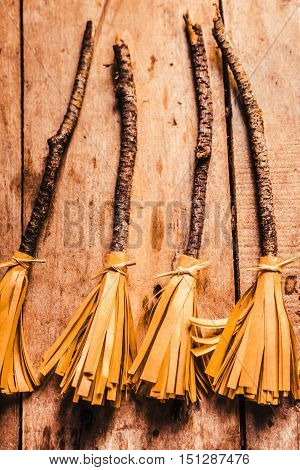 Still life halloween photo on witchcraft broom sticks made of old leaf on wood background. Autumn crafting