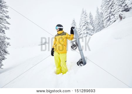 Portrait of male snowboarder wearing helmet with glasses, yellow jacket and pants, black gloves standing with snowboard in hand and planning freeride route  - snowboarding and extreme sports concept