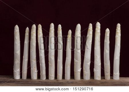 row of white asparagus on black background