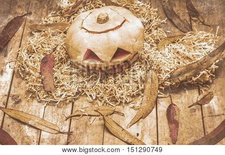 Horrific evil face carved into a halloween pumpkin on dry grass and autumn leaves over wooden plank expressing frightening face