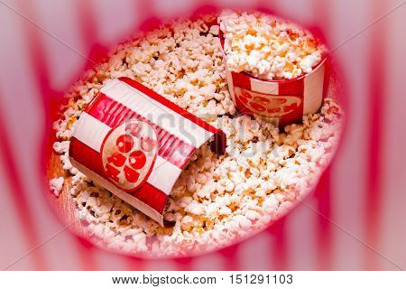 Striped red and white containers with pop corn through snack bar window. Movie foods
