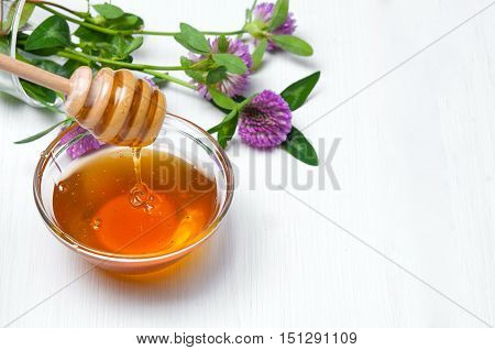 Honey and wild flowers on white wooden background. Copy space