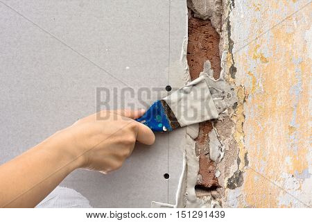 hand with spatula plastering wall during repair
