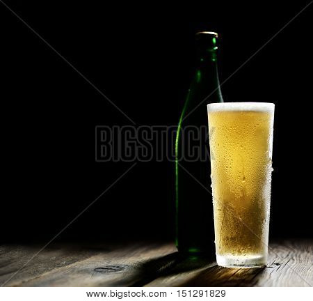 he cold frothy beer in a glass and a green bottle on a dark wooden background