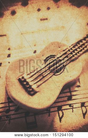 Sepia toned weathered close up on single little carved guitar on sheet music. Folk songs
