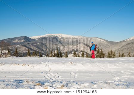 Hiker man in the winter mountains using gps receiver for planning a route. Wonderful winter day.