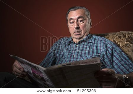 Senior elderly man shocked with news he's reading in the newspaper, red background