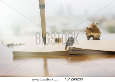 Closeup of brown spiral notepad and pen on blurry background