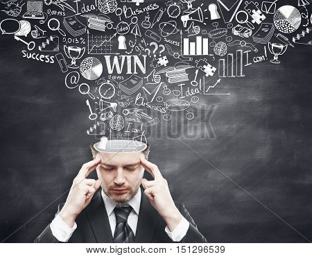Pensive young businessman with business sketch coming out of his head on blackboard background. Brainstorming concept