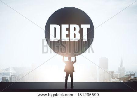 Struggling businessman holding huge ball on bright city background. Debt concept