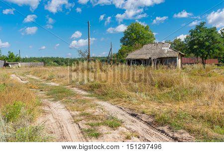 Landscape with sandy road and abandoned house in depopulating village Hetmanka Poltavskaya oblast Ukraine