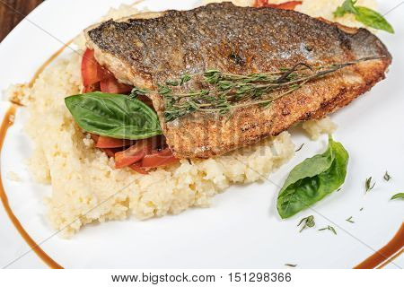 Whole roasted Dorado fish with couscous herbs and tomato salad Arabic dish