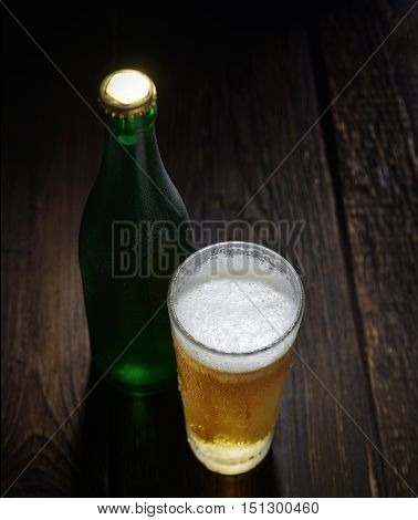 The cold frothy beer in a glass and a green bottle on a dark wooden background