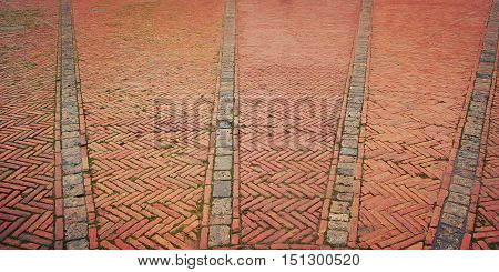Brick pavement. Historic center of Siena. Piazza del Campo. Old zigzag pavement with grass growing through. Old paving useful as a background. Italy.