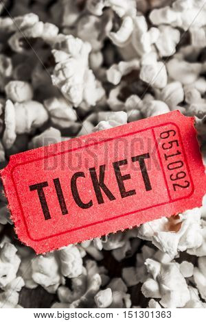 Show scene of a retro red ticket lying on pile of popcorn. Event entry