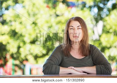 Serious Woman Seated At Table Outside