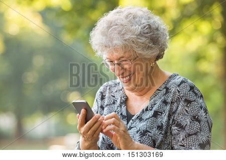 Smiling elderly woman with spectacles and typing phone message while sitting at park. Senior woman using wireless internet connection on smart phone. Happy old woman looking at screen on smartphone.