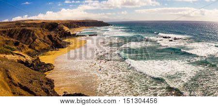Young People Surfing On La Pared Beach With Vulcanic Mountains In The Background On Fuerteventura Is