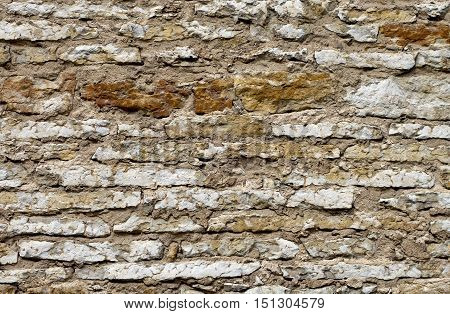 Damaged by weather ancient limestone wall background.