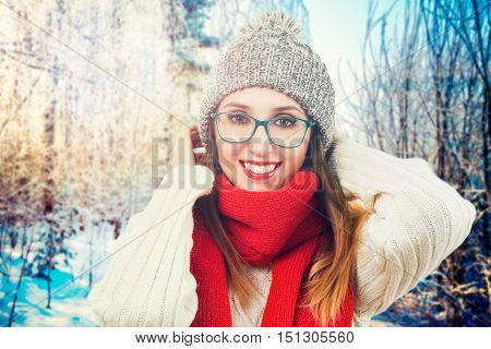 Happy Smiling Girl in Red Scarf, Sweater and Beanie Hat in Snowy Park at Sunset. Fashion Woman in Winter Outdoors Concept. Backlit. Toned Photo.