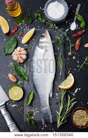 Raw fish, sea bass on slate black board. Ingredients for cooking, grill, roasting. Top view Copy space