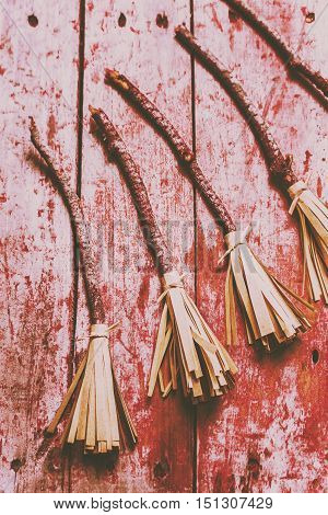 Creative red splattered witch broomsticks on a rustic wood background. Gathering of evil witches