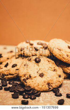 Yummy brown toned chocolate chip buscuit cookies on kitchen bench with scattering of cooking choc droplets