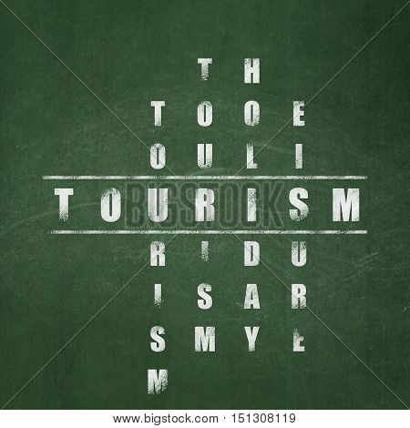 Travel concept: Painted White word Tourism in solving Crossword Puzzle on School board background, School Board