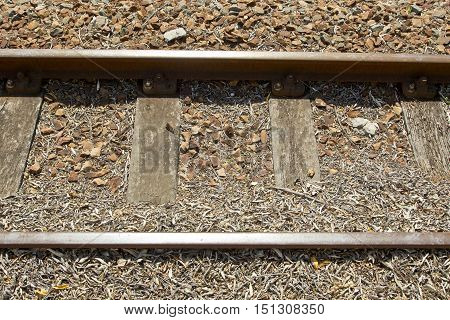 close up of a train track with sleepers and stones in bright sunlight