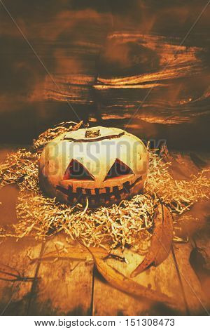Scary background still-life image of a country pumpkin head shrouded in orange mist and woody leaf details. Fall of Halloween