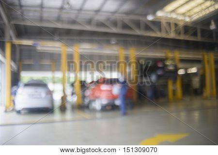Blurred of car technician repairing the car in garage backgroundcar repair station.