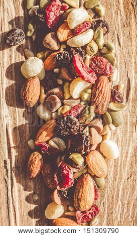 Rustic country food artwork on a mix of dried fruits nuts seeds and chocolate on wooden bench