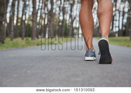 Young woman running outdoors in a city park on. motion blurred image color toned image. feet close-up