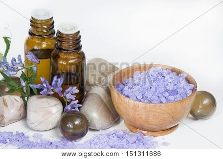 violet bath salt in wooden bowl and two vials of aromatic oil