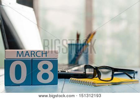 March 8th. Day 8 of month, calendar on business office background, workplace with laptop and glasses. Spring time, empty space for text.