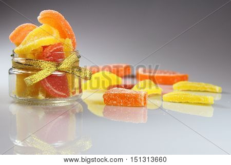 marmalade color in a glass jar on a white table