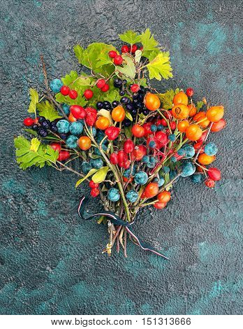 Bouquet of wild berries on a textural background top view with copy space
