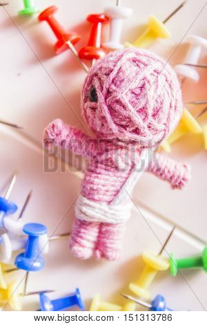 Little baby doll made from pink yarn surrounded by white blue yellow and red pins. Mummy voodoo
