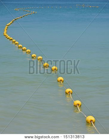Chain Of Yellow Buoys In Blue Sea Water