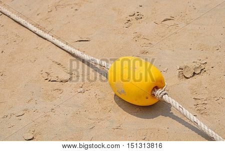 Yellow Marker Buoy On Sand Beach