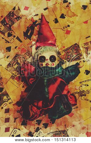 Demonic possessed Joker doll on a blood splattered background of playing cards. Evil dolls