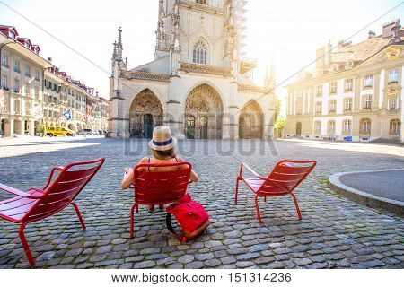Young female tourist sitting on the red public chairs on Munster square in the old town of Bern city in Switzerland