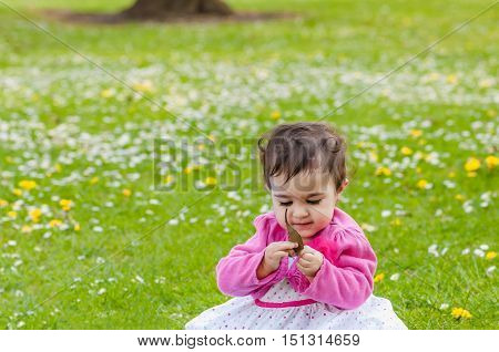 Cute chubby toddler looking at a leaf curiously exploring nature outdoors in the park