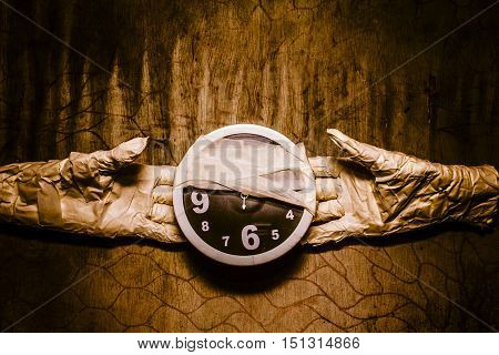 Mummy hands showing bandaged clock on grunge copy space wall. Halloween time coming soon