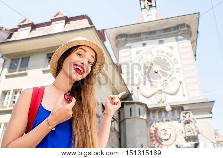 Young female tourist in front of the famous clock tower in the center of the old town of Bern city in Switzerland. Having a great vacations in Switzerland